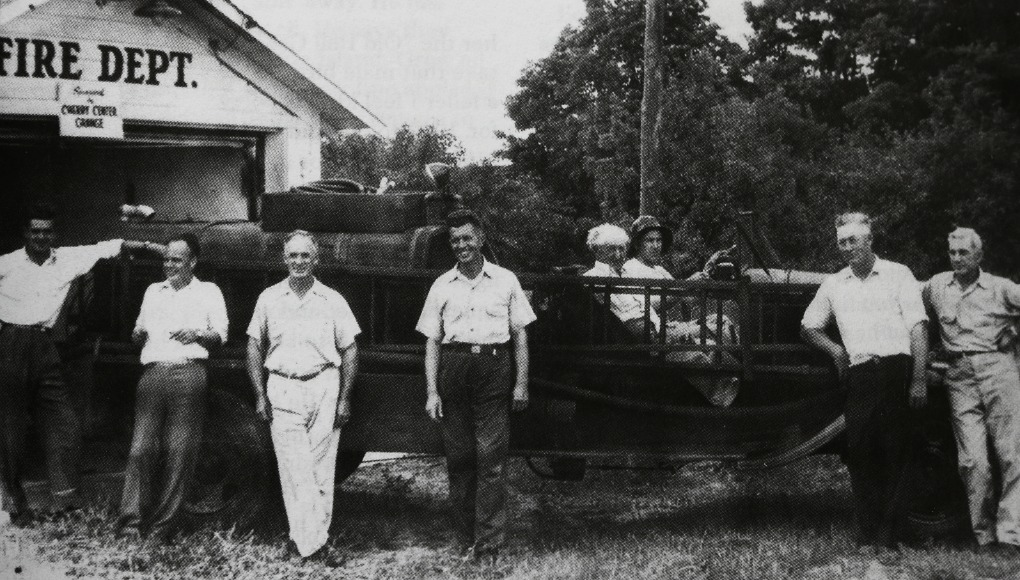 """Peninsula Fire Department, Circa 1945; this photo was taken at the """"fire barn,"""" located on Center Road, just north of the current fire hall in Mapleton. Pictured, standing left to right: Harry Heller, Arnold White, Roy Hooper, Claude Watson, Stanley Wood and Ray Heller. Seated in the truck are John Lardie (wearing helmet) and Ike (Isadore) Lardie 