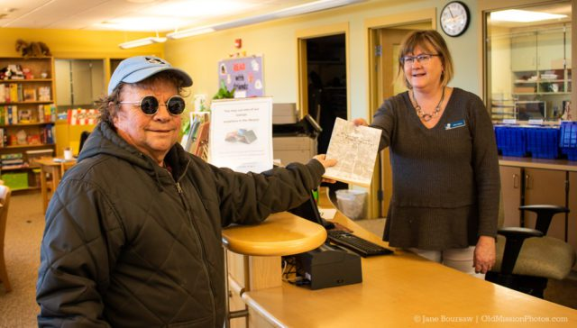 Tim Boursaw gives a copy of his Uncle George Boursaw's book, Migrant Times and Other Musings, to PCL staff Cathy Adams