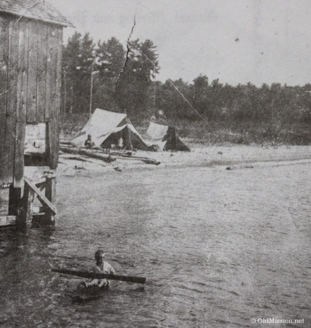 Chum Reay paddling on a raft in Old Mission Harbor in 1910, next to a fish shanty and Native American camp on Haserot Beach