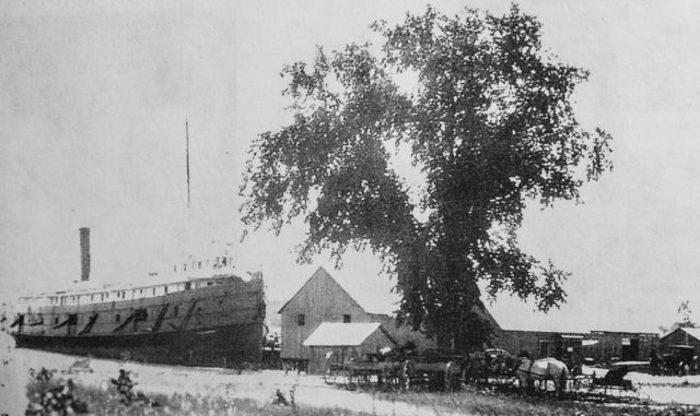 Ship docked at Old Mission Harbor, 1800s. In the shade of the tree are horses, wagons and carriages all waiting for their fare.