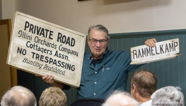 Bob Rosi Holds Signs from the Illinis Cottagers Resort at a presentation of the Old Mission Peninsula Historical Society