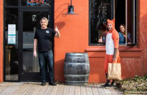 Guy in a Fox Suit gets takeout from Peninsula Grill; Also pictured, Johnny Rokos and Grill owner Jennifer Davies | Jane Boursaw Photo