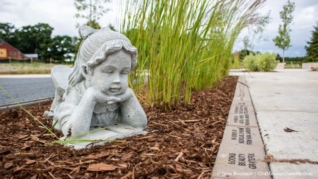 Girl with a book overlooks memorial bricks at the Mack and Lorraine Beers Children's Garden at Peninsula Community Library on the Old Mission Peninsula | Jane Boursaw Photo
