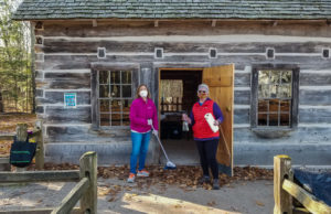 Jane Boursaw and Phyllis Cooley close up the Hessler Log Cabin at Lighthouse Park on the Old Mission Peninsula | Ginger Schultz Photo