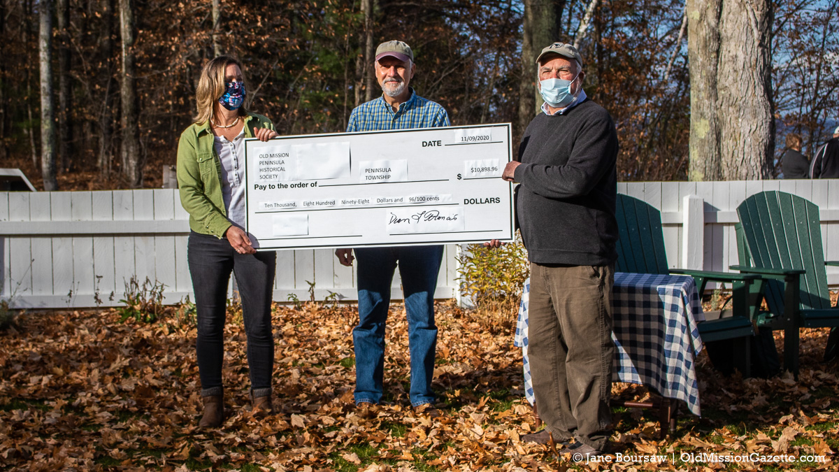Peninsula Township Clerk Becky Chown, left, and Supervisor Rob Manigold, right, accept a check from Old Mission Peninsula Historical Society member Chris Rieser at Mission Point Lighthouse | Jane Boursaw Photo
