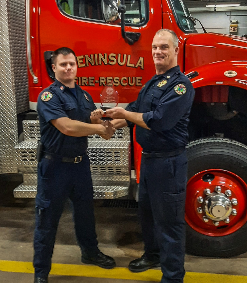Peninsula Township Fire Department's Lt. Ethan Passalacqua receives the Firefighter of the Year Award from Fire Chief Fred Gilstorff | Fire Department Photo