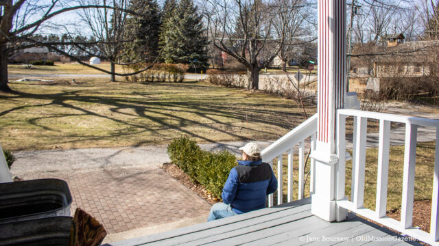 Tim Boursaw on the steps of the Old Mission school house, 65 years later; log church on the right and former Bee house across the road | Jane Boursaw Photo