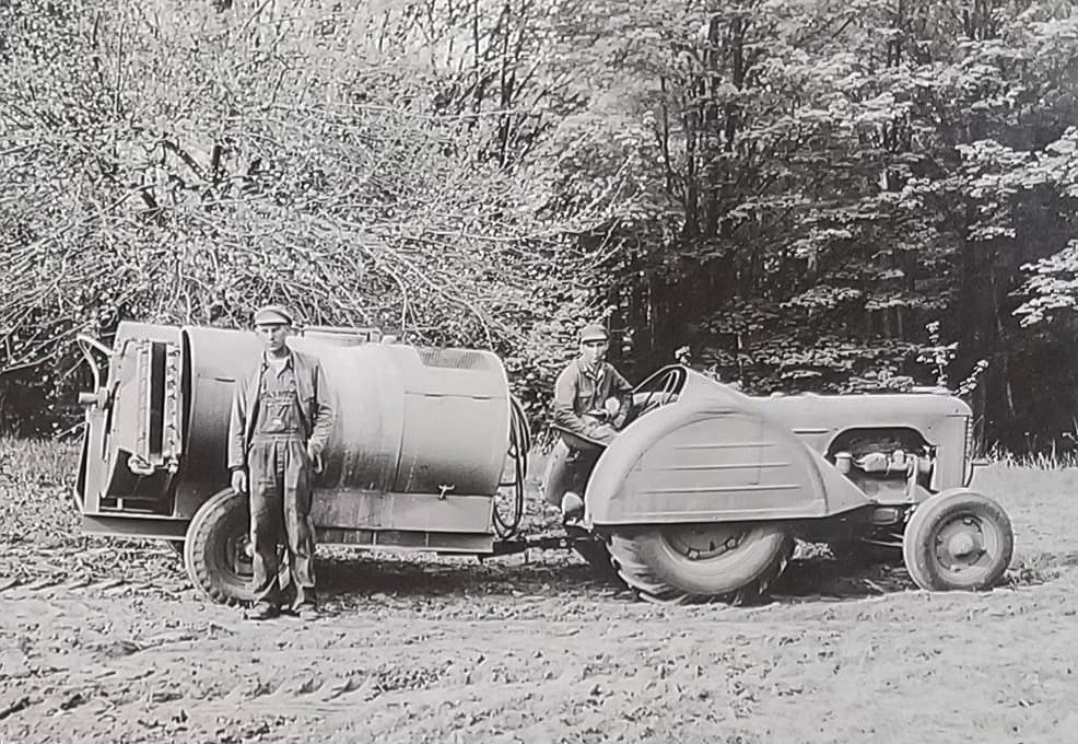 Walter Johnson, standing, and his brother, Guy Johnson, with their Case DO tractor and sprayer, circa late 1940s or early 1950s