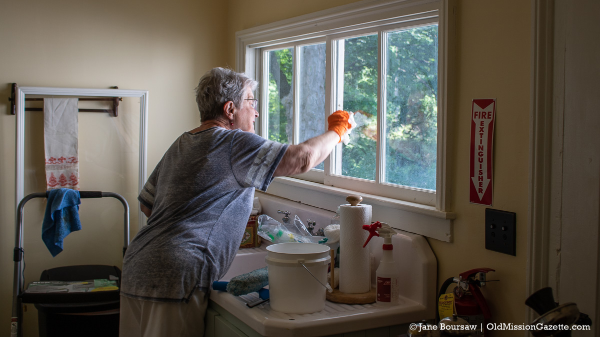 Judy Weaver washes windows in the kitchen at the Historic Dougherty House in Old Mission, Michigan | Jane Boursaw Photo