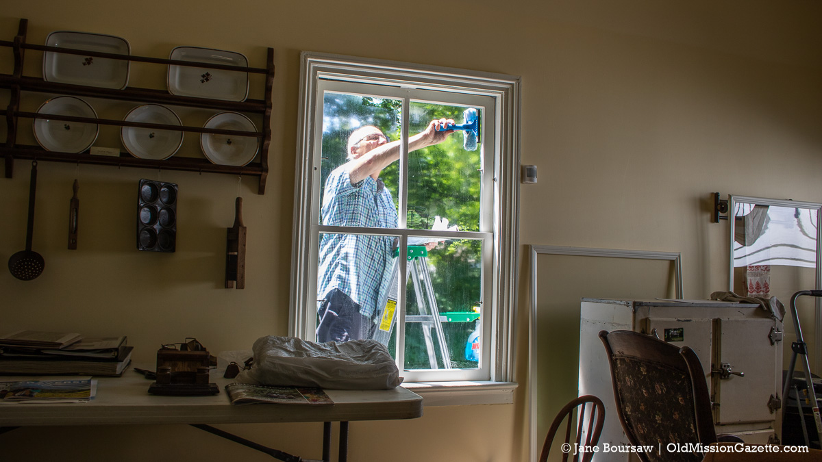 Chris Rieser washes windows at the Historic Dougherty House in Old Mission, Michigan | Jane Boursaw Photo