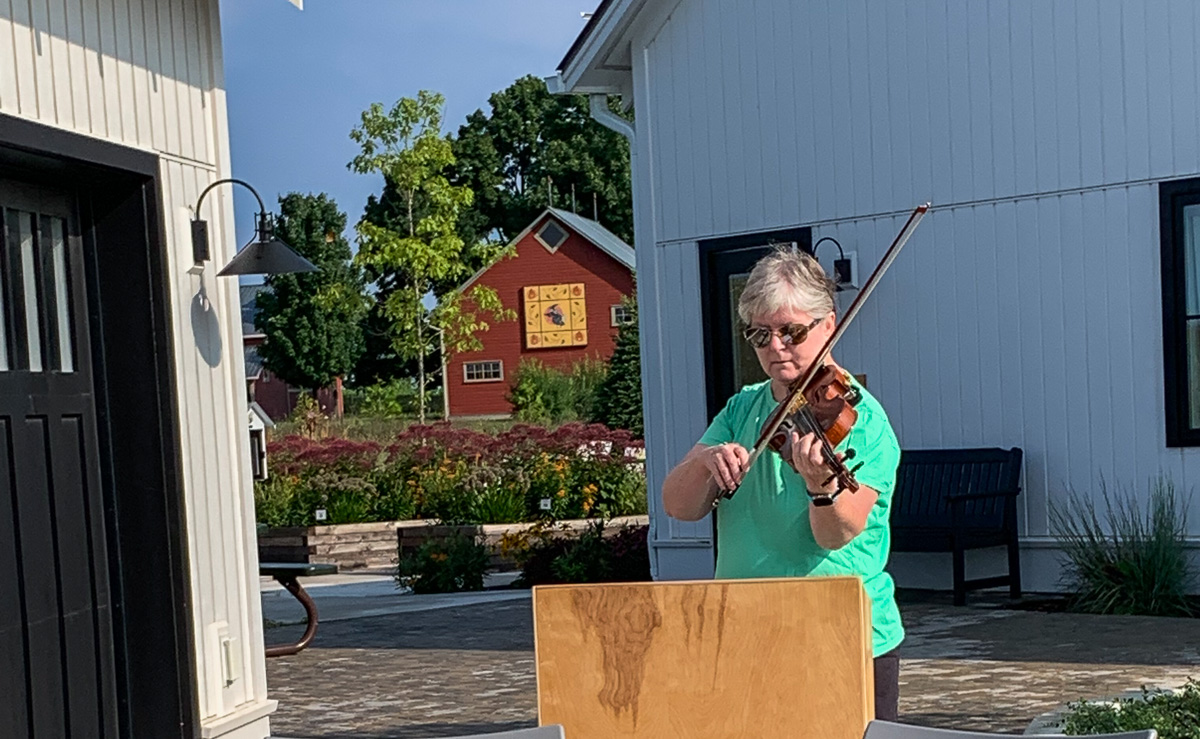 """Jane Boursaw plays """"Ashokan Farewell"""" at the Covid Memorial Tree Planting at Peninsula Community Library, in cooperation with the Old Mission Peninsula Historical Society Tree Planting Committee 